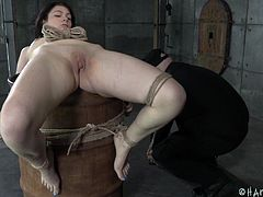 She's a cute brunette and loves to be used like a sex toy. Our executor has some special plans with her but first, he needs to prepare her. After he tied her up in an uncomfortable position, he decides to change that so he ties the chick on a barrel and keeps her legs spread. Yeah, she looks better that way!