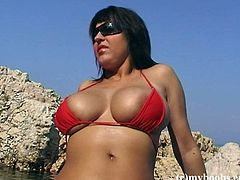 Gorgeous brunette Kora Kryk, wearing a sexy bikini, is having a photo shoot on a sea shore. The milf shows her breath-taking natural jugs for the cam and seems to enjoy herself.