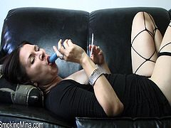This horny MILF takes care of all of her fetishes at once. She wears fishnet stockings while fucking her toy and smoking.