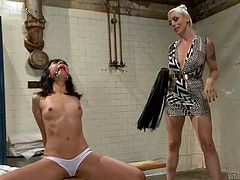 This slave girl is in the locker room with a gag in her mouth. Lorelei is going to whip her slave into submission. She whips her slave's chest and tits, and then fingers her went cunt in such a mean way.