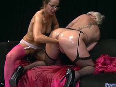 Two frisky lesbians oiling up each other and stretching pussies