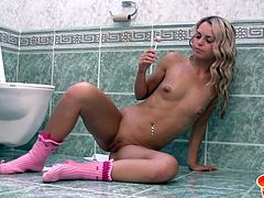 Cute blonde girl Sabrina is sitting on the bathroom floor wearing nothing but a pair of socks. She has her legs spread wide open so that she can play with her pussy. She sticks her candy lolly inside her cunt hole and then licks the pussy juice off of it. It tastes so good. She loves masturbating.