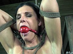 This dirty milf slave is tied up in rope and gagged so she can't scream or move while her master tortures her. She gets her nipples pinched with a pair of scissors and then a pole pushed against her nether regions.