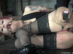 Cadence is kept captive down in the basement. The slutty short-haired redhead is wearing a mouth gag, chains, kinky stockings and high heels. The dirty game involves making her suffer. There are also a vibrator and a dildo used to create lusty pleasures. See the bitchy tattooed babe ass-whipped without mercy.