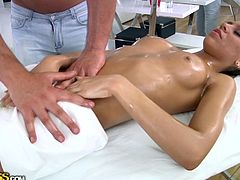 This russian brunette is lying on the massage table while this lucky guy gets to oil her sexy body. He plays for a while with her sexy legs, when he notices the bitch is turned on. He oils her breasts and rub her nipples softly. She turns over, spreads her long legs while he touches her. She grabs his dick and he begins to rub her wet cunt.