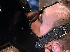 This white slave is tied up and covered in leather in the sex dungeon by the cruel black mistress. She whips his ass until it is nice and read. He is gages so her can yell for help. She grabs his cock hard and sits on his face.