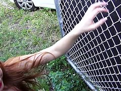 This dirty redhead slut was stranded so I picked her up for a ride. She drove with me for a while, and then we stopped by a fence in the alley. She pulls her panties down and lets me fuck her deep from behind. She gives a great blowjob, too.