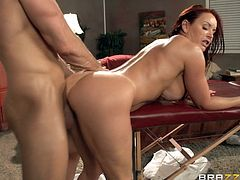 Redhead gets oiled up, massaged and fucked hard on the table