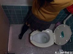 This cute Japanese schoolgirl gets horny, so she stops in a bathroom on her way home and plays with her pussy, while she sits on the toilet. She moans and shakes, as she flicks her beans with her panties around her ankles.