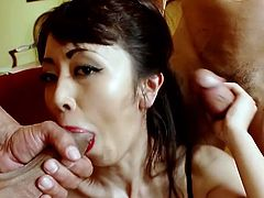 Asian seductress wearing fishnet stockings gives blowjob to a duo of horny guys