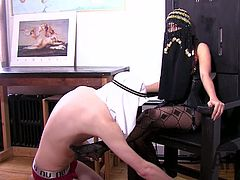 This mistress has an oriental look. She plays with her Arab slave. He worships her sexy feet first. Then she tortures his cock and burns him with hot wax. She also fucks his butt.