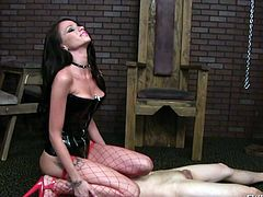 Who said women cannot be dominant? The next kinky scenes shows a hot brunette, wearing a black latex top, red fishnet stockings and very high heeled shoes. Slutty Raven frees the naked man only to ask him to lay on the floor. She is sitting on his face, while he eats her wet horny pussy. Enjoy the details!
