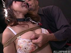 She is tied up by her master with rope and made to look, like a dirty slut by him. Her big natural tits are hanging out and she is collared, and has her nipples pinched. She doesn't even have her panties taken off, after having a sex toy in her butt.