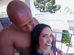 Playful sexy chick Tia Cyrus in blue bikini flaunts her round butt and shows her camel toe before she takes huge black dick in hand. She strokes black dudes massive dick and gives head on the balcony.