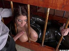 Huge boobed mouth-watering babe Brook Ultra in latex outfit gets caged and face fucked by hot guy. She demonstrates her amazing melons as he bangs her hot mouth through the bars.
