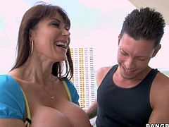 Hot bodied MILF Eva Karera demonstrates her trimmed bush and her perfect huge fake tits before she gives blowjob on the balcony. Then she gets her snatch drilled on the bed.