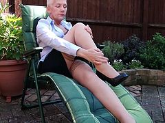 54 year old Fleur has just got home from the office and she is going to relax in her backyard. She sits on her lounge chair and opens her top a little bit, to reveal her massive breasts. The mature slut shows off her sexy pantyhose, too.