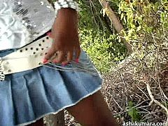 Asha is so horny that she cannot wait until she gets home. She sits down on the side of the road and slides her hands underneath her jean skirt, to rub her vagina. She plays with her pussy and rubs like a horny slut.