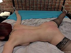 A busty redhead babe wearing stockings gets her hands and legs tied with ropes. She stands face down laying on the sheets. A dominant horny guy begins to fist deeply her ass hole. He also attached clothespins to her arms. Moaning is useless, as the helpless slut wears a ball gag... See the kinky details!