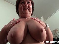 Shorthaired mature slut plays with her huge tits and pussy