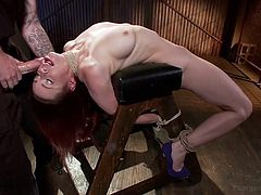 In the brutal sex dungeon this dirty slave is treated in the most humiliating way. She is tightly tied up with rope. The restraints are so tight around her body and neck, as her back is arched over the stool she is tied to. The mean master sticks his cock down into her throat and face fucks her.