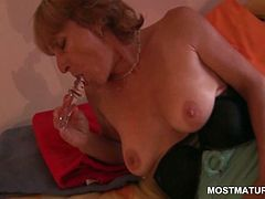 Attractive blonde mature nailing her pussy with a glass dildo