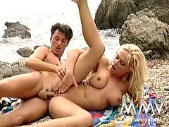 Big titted blonde gets her pussy, licked, fingered and fucked, all on a public beach during the day.