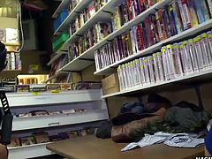 A wild orgy breaks out in a DVD shop after the girls start flashing their tits and pussies.
