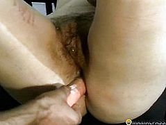 The woman pushes her anal toy