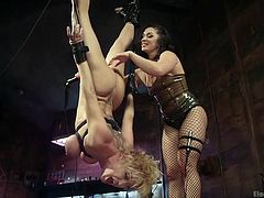 Lea is hanging by her feet upside-down, while her mistress is using a vibrator on her pussy, making her wetter than she already is. She loves teasing and torturing her subject, making her moan and scream with delight. Her nipples poke out hard and her tits look even bigger, being wrapped by straps.