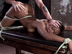 The image of this slutty ebony babe, tied up with strong unbreakable ropes on a table, is a really inciting view! See Chanell's hot pussy being tormented with the help of a kinky dildo, while immobilized by a bad-intentioned executor, who keeps her mouth shut and her fear growing!