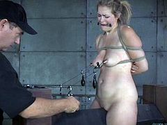 Horny dominant dude pins nipples of submissive tied up blondie with metal stuff