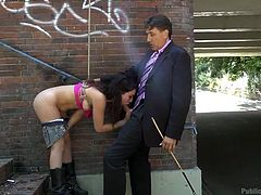 Slutty Juliette has been tied up strongly with ropes. While left waiting on the stairs in public, she begins to play with her small tits, until a horny man arrives... The humiliated brunette is eager to suck his dick, hoping that she will eventually get freed.