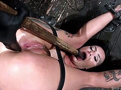 Slutty Lola finds herself completely helpless in front of a merciless executor, who only wants to make her suffer a terrible torture. He makes the busty tattooed brunette suck a dildo and stops, only to stuff it in her lovely cunt, while also using a kinky vibrator. Enjoy the brutal orgasm!