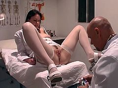 Doctor inserts speculum in rosy-titted nurse's wide-open cunt