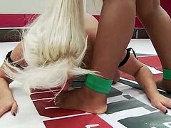 Yasmine dominates slutty Holly in the wrestling arena. The ebony bitch with impressive tits is wearing a kinky strap on, while the blonde milf is on her knees... The atmosphere on the wrestling arena gets hotter, as the tattooed lesbian slut gets banged from behind!