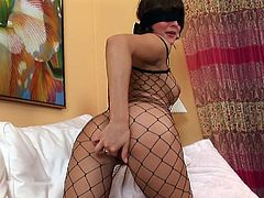 Fishnet body stocking girl wears a blindfold as she masturbates