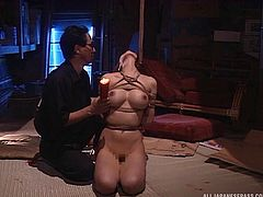 Pretty intense bondage as she is tied up and splashed with hot wax