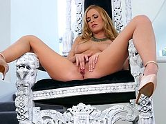 This bitch with golden hair and long legs, seems to enjoy being filmed, while playing with herself. The busty attractive babe starts to undress with provocative movements, then gets her crazy ass on a comfy royal chair. See this horny princess, spreading legs widely and masturbating with frenzy!