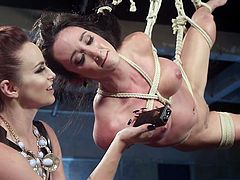 Lovely Virginia is gorgeous enough to fuck from any position, even hanging in midair, tied by ropes and suspended from a ring by the same. Bella is her mistress and she keeps stuffing Virginia's bushless cunt with electric toys, giving her vibrations and shocks, to make her moan, scream, and cum very hard.