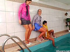 Inviting girls play seductively in a pool with their wet apparel sticking on their flawless bodies