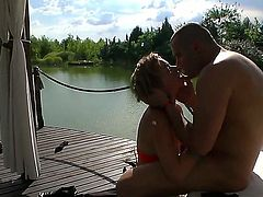 Blonde with huge tits is sucking a cock by the body of water. She loves it when her body is nude in the sun while she is taking on a hard dick.