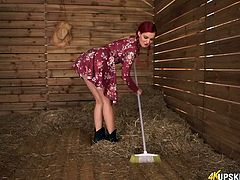 Redhead in a short dress teases in the barn
