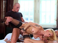 Pretty and petite blonde porn star Stacy Silver stripping out of her sexy bra and panties, then getting double penetrated by two hung guys on a bed while wearing black stockings and stiletto high heels.