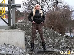 Blonde beauty in leggings pees by the railroad track