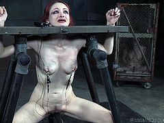 Violet gets herself in over her head this time. She's bound in an unrestrained stocks, while positioned over a dildo. Clamps are sharp on her nipples, and movement pulls on them. She's being filled, but the price is pain.