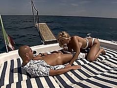 Bronze blond wearing white bikini gives blow job on a yacht
