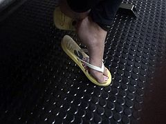 Feet in yellow flip flops play in subway station foot pieds