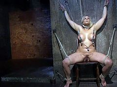 Angel is bound and being pained, as well as pleasured by her executor. She has a rope around her neck, clamps on her nipples, and her arms above her head. Nothing can stop him from using a vibrator on her, as she cries out from the clamps, which are weighted down.