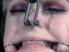 Anna is imprisoned here at Infernal Restraints, and her main pains are coming from the hooks attached to lines, that are currently pulling her mouth and nose. She gets re-positioned later, although it's unknown what will happen to her then.